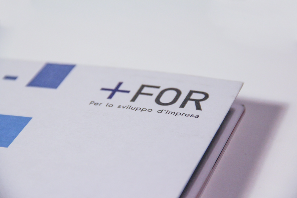A detail of the For Plus logo on the cover.
