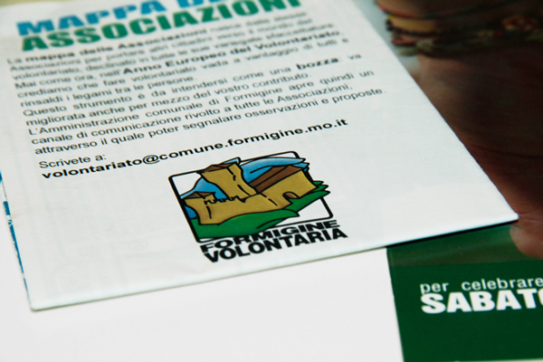A detail of the closed flier. On the front, the colored logo of Volunteering in Formigine stands out, right below a brief description of the project