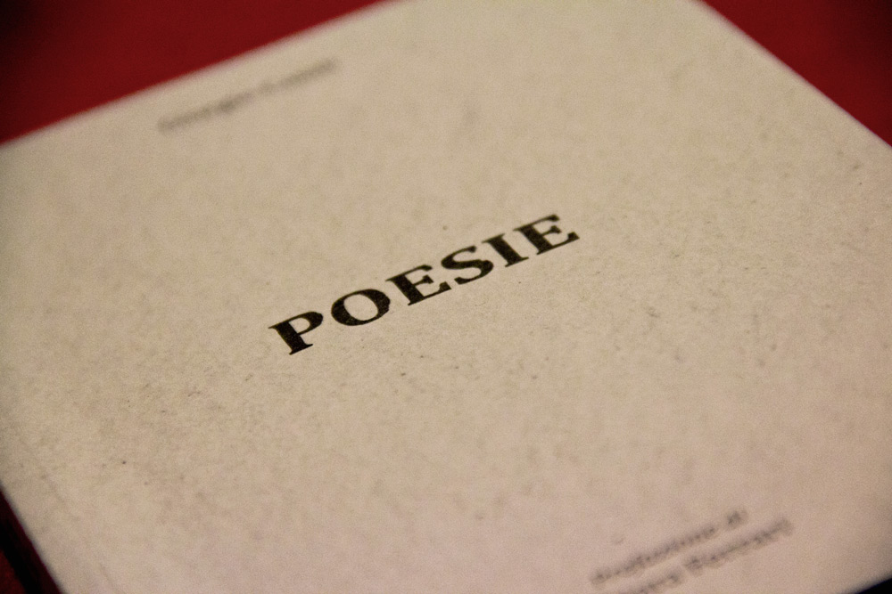 "A detail on the book cover, the title ""poesie"" (poems) in the centre, written with a vintage font and some light stains in order to embellish it. The cover of rough paper consists of only a few elements, a way to emphasize this single central element and to enhance its meaning."