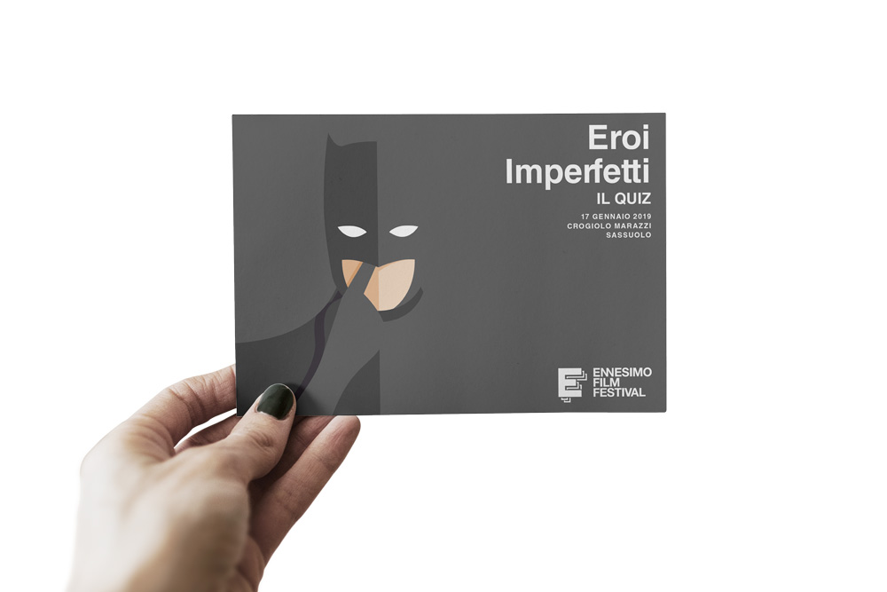 Imperfect Heroes: the final format of the postcard. A hand is holding the postcard used to make question during one of the showcase nights. Specifically, in this case one can clearly see Batman picking his nose, the name of the night and the Ennesimo Film Fesitval logo.